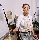 portrait of a painter in an apron sitting beside an easel