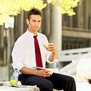 portrait of a businessman sitting eating a sandwich