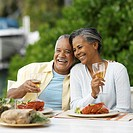 portrait of a mature couple sitting at an outdoor dining table