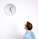 young man looking at a wall clock