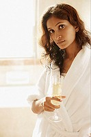Woman in bathrobe, holding champagne glass, looking at camera