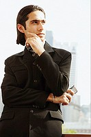 Businessman with arms crossed and hand on chin, looking away