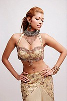 Young woman in Indian costume, hands on hips, looking down