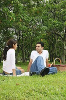 Couple in park, sitting on grass, picnic basket next to them