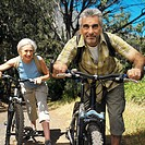 close-up of a mature couple pushing bicycles up a hiking trail