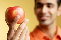 Man holding apple in hand, selective focus