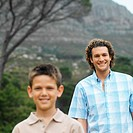 portrait of father and son smiling standing outdoors