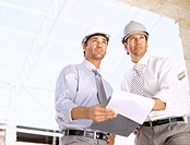 architects holding a clipboard at a construction site