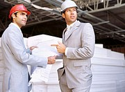 side profile of two architects holding blueprints at a construction site