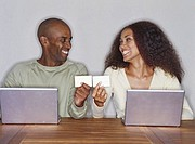 young couple using laptops and holding business cards