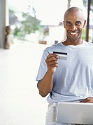 portrait of a young man using a laptop and holding a credit card