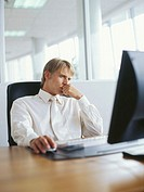 businessman sitting in front of a computer and thinking in an office