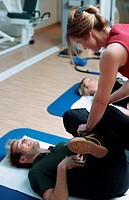Young man at the fitness studio, gym, working out, doing exercises, making gymnastics on a mat, instructed by a coach, trainer