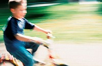A little boy riding a bicycle, driving a cycle (thumbnail)