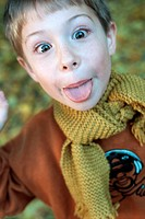 Little boy in the autumnal wood, forest, sticking out his tongue