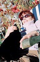 Woman outside in the autumnal garden, sitting in a deckchair with a cat on her lap
