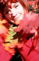 Little girl in the garden behind coloured leaves (thumbnail)