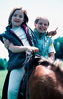 Two girls riding a horse, sitting in the saddle