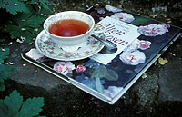 A cup of tea and a book about roses