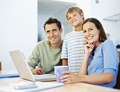 parents with their son sitting in front of a laptop