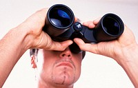 Portrait of a young man, 20-25 25-30 30-35 years old, looking through binoculars, a spyglass (thumbnail)