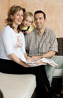 A young couple, young man and young pregnant woman, 25-30 30-35 35-40 years old, sitting on the sofa with their little daughter, 1-5 years old