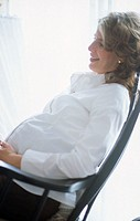 A young pregnant woman, 25-30 30-35 35-40 years old, sitting in a rocking chair