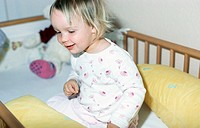 A little girl, 1-5 years old, sitting in it's bed (thumbnail)