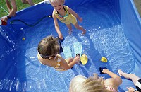 Three children, girls, 5-10 years old, playing in the garden in a swimming pool in the garden