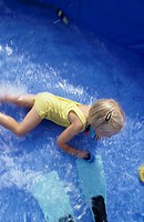 A child, little girl, 5-10 years old, playing in a swimming pool in the garden