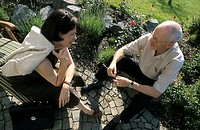 A senior, businessman, 45-50 50-55 55-60 years old, and a woman, businesswoman, 40-45 45-50 years old, sitting in a summerly garden, talking
