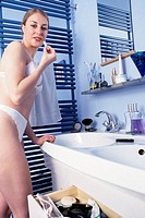 A young woman, 20-25 25-30 years old, in the bathroom, putting lipstick on her lips