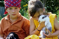 Two children, a boy and a girl, 5-10 years old, in the garden in summer, holding rabbits, bunnyies in their arms