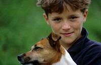 A boy, 5-10 years old, and a dog outside