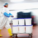 Side view of female worker pushing a trolley of containers