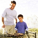 portrait of a father and son cooking on an outdoor barbeque grill