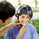 close-up of a man strapping a helmet on for his son (12-14)