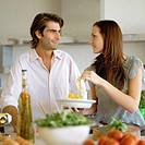 Young couple preparing salad at kitchen counter