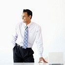Businessman standing at an office desk smiling with one hand in his pocket
