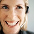Close-up of a young businesswoman wearing a telephone headset and smiling