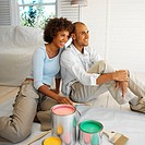 Young couple sitting together on the floor with paint buckets and paintbrushes