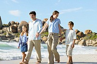Portrait of a young couple with two children (8-12) walking on the beach