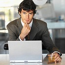 front view portrait of businessman holding a glass of whiskey with laptop on desk