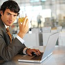side view of a businessman drinking a glass of whiskey sitting at desk and working with laptop