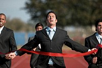 businesspeople running towards finish line