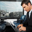 businessman at airport terminal using laptop with view of airplane through window