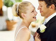 side profile of a newlywed couple looking at each other and laughing