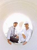 two male architects sitting in a pipe