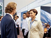 businessman and a businesswoman talking to each other at an exhibition