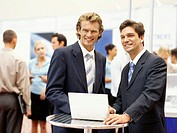 two businessmen standing in front of a laptop at an exhibition